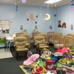 Infant care room with cribs, mobiles, and toys