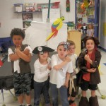 Children dressed as pirates with a pirate ship they built from a table