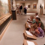 Young children at museum drawing their own rendition of a famous painting