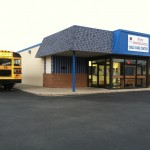Exterior of First Impressions Child Care Center with school bus in parking lot
