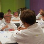 Children painting pictures wearing white smocks